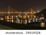Reflections from bridge lights and boats on the water beneath the bridge - stock photo