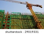 A large construction crane works to complete a new high rise in a Chinese city - stock photo