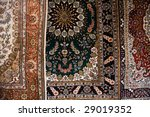 Close up image of 3 ornate Persian style carpets made in Kashgar China - stock photo