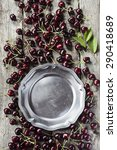 Small photo of Cherries background with pewter plate with copy space