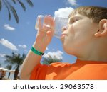 Boy finishing drinking from a plastic glass - stock photo
