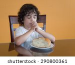 Small photo of Child praying for the daily bread: Curly-haired boy sits and prays with eyes closed and hands together before eating a piece of bread placed before him on the dining table.