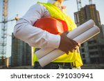 Small photo of Closeup photo of man in shirt and jacket holding hardhat and blueprints on building site