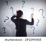 Small photo of Business woman write question mark on the wall. She dont know what to write