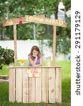 Bored young girl with no customers at her lemonade stand - stock photo