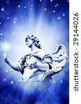 mystical angel touching star over blue background with divine rays of light - stock photo