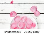 Stock photo pink rose petals in bowl of water on rustic background top view 291591389