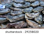 Close-up of a basket of fresh oysters for sale at a French fish market