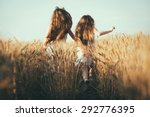 Two Girls Outdoors Raising...