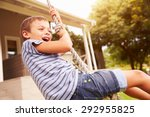 Smiling Boy Swinging On A Rope...
