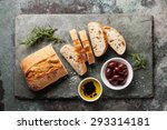 Small photo of Fresh ciabatta with olive oil and olives on stone slate background