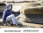 Boy sitting on rocks. Young boy in blue jacket sitting on rocks gazing into the distance at the seaside. Taken in Whitley Bay in North East England - stock photo