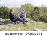 Mother and Daughter. Mother and teenage daughter sitting down, chatting and smiling during a hillside walk, relaxing together. Outdoors lifestyle. - stock photo