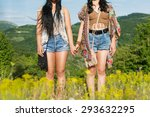 Two Young Hippie Women Holding...