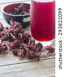 Small photo of Roselle juice on wooden background, roselle juice in glass on sack