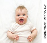 Small photo of Smiling baby lying on a white bed. Good morning!