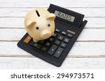 Small photo of Calculating your rates, A golden piggy bank on a calculator with word Rates over a distressed wood background