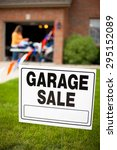 Small photo of Garage sale sign on the front yard of a suburban home with a woman looking at items on a table.