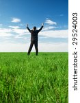 glad businessman in black costume standing at the green grass - stock photo