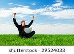 successful businessman with laptop sitting at the green grass - stock photo