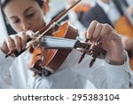 woman tuning her violing and... | Shutterstock . vector #295383104