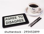 Small photo of Business Term / Phrase on Tablet PC with a cup of coffee and pens on a White Background - Black Word(s) on a white background - Agree To Disagree