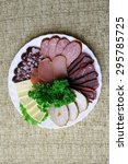 Small photo of White dish with meat and salami appetizer. Decomposition evenly coats. Plate stands on a table covered with a tablecloth.