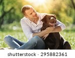 Stock photo young guy with retriever on walk in summer park 295882361