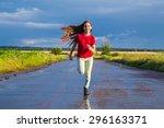 happy girl running on wet road... | Shutterstock . vector #296163371