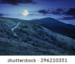 summer landscape. road through pine forest on hillside meadow to the mountain peak at night in full moon light - stock photo