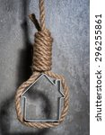 Small photo of Small house framed with hangman's noose hanging over the grey concrete wall