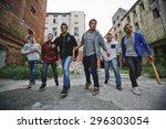 Small photo of Group of spiteful hooligans walking along grunge brick houses