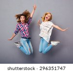 two cheerful girls jumping over ... | Shutterstock . vector #296351747