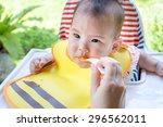 baby girl eating baby food | Shutterstock . vector #296562011