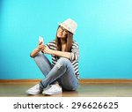 young woman sitting on floor... | Shutterstock . vector #296626625