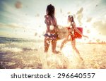 two ladies running into the sea ... | Shutterstock . vector #296640557