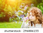 a little girl blowing soap... | Shutterstock . vector #296886155