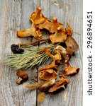 Small photo of Arrangement of Dried Forest Chanterelles, Porcini and Boletus Mushrooms with Dry Grass, Stems and Leafs closeup in Rustic Wooden background