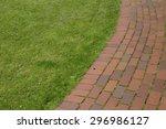 Brick Pathway Next To A Grassy...