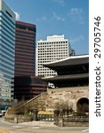 600 year old pagoda style Namdaemun City Gate in central Seoul with modern buildings. - stock photo