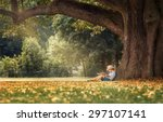 little boy reading a book under ... | Shutterstock . vector #297107141