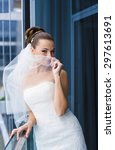 Small photo of Attractive bride is standing near the window, looking jilt and smile.