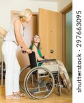 Small photo of Happy women in wheelchair with female assistant at threshold