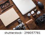 Work space for photographer, designer or hipster style. Have a laptop, film camera, film, speaker, glasses, book, pencil on wooden table. - stock photo