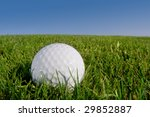 golf ball resting on grassy bunker with blue sky background - stock photo