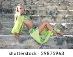 Beautiful belly dancer in green on the ancient stairs of Kurion amphitheatre in Cyprus. - stock photo