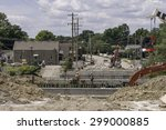 Small photo of WARRENVILLE, ILLINOIS, USA - July 22, 2015: Workers realign a branch of the DuPage River to prevent local flooding during a project to replace an old bridge with a new one for better traffic flow.