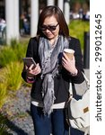 woman looking at phone walking... | Shutterstock . vector #299012645