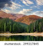 lake near the pine forest in orange autumn mountains - stock photo