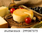 Cheese Wheel On Wooden Cutting...